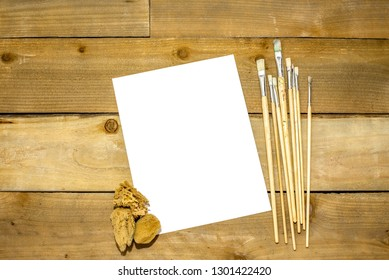 Paint brushes on a rustic distressed wooden background