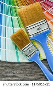 Paint brushes pantone fan on wooden board.