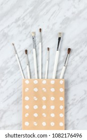Paint brushes in a paper bag with white circles painted on it, on marble background.