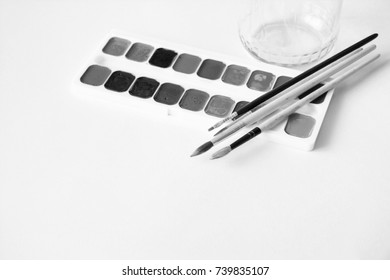 Paint brushes and a set of paints black and white