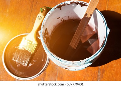Paint bucket and brush and colors available. Paint and brush on the Pine wooden background with light.