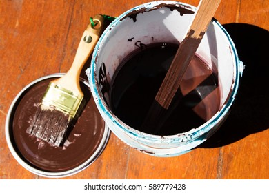 Paint bucket and brush and colors available. Paint and brush on the Pine wooden background.