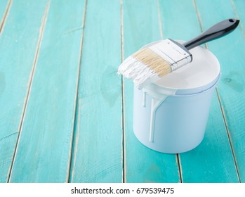 Paint bucket with paint brush on the old wooden background with copy space