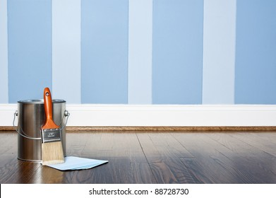 Paint can and brush against a blue striped wall