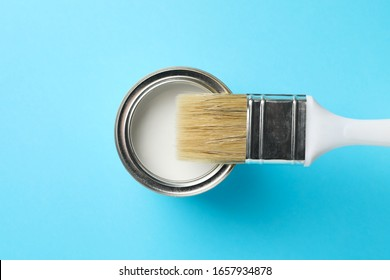 Paint can and brush on blue background, top view