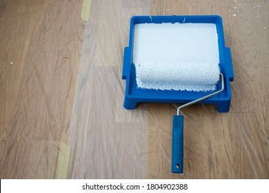 Paint can, roller and paint tray on oak floor covered with transparent plastic film .  Paint roller on tray blue color background. Top view