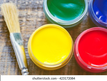 paint cans with brush on a wooden background top view
