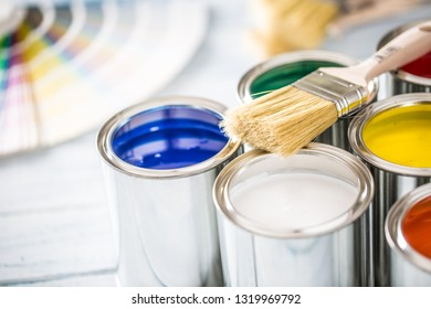 Paint cans brushes and color palette on table.