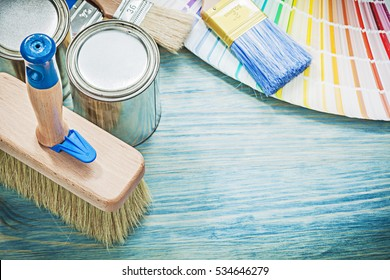 Paint cans brushes pantone fan on wooden board construction concept.