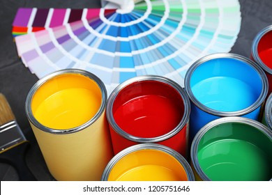 Paint cans and color palette samples on table, closeup