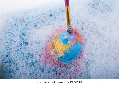 Paint dissolving through painting brush on the top of globe