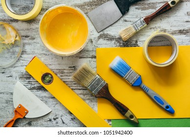 Paint for house decor with brushes and accessories on the desk. Interior improvement tools, view from above.