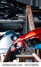 Paint job. New red color, car repair service, maintenance facility, garage. Vertical portrait mode, blurry background,industrial interior, natural daylight. Occupation, job, production line, interior.