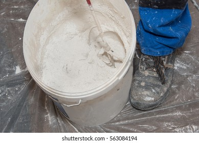 Paint mixer and bucket on covered floor