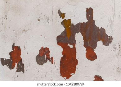the paint is peeling off the gray wall. close-up of orange and brown paint can be seen from under the shabby paint, abstract background