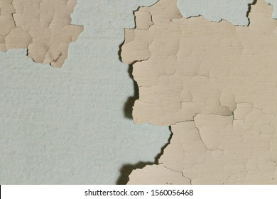 The paint is peeling, the wall as a background, the old coating, expressive cracks in the paint.