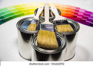 Paint pot samples with brushes on it and color samples in backgrpund