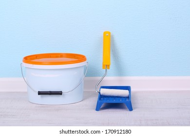 Paint and roll on floor in room on wall background