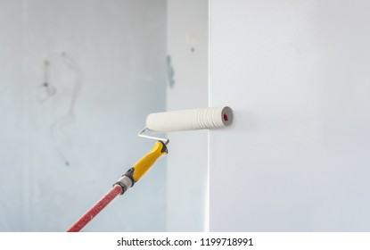 Paint roller applying paint on white wall, home improvements.