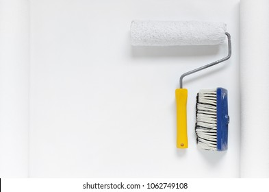 paint roller and a brush on white wallpaper roll with copy space