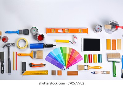 Paint roller with color swatches and other tools on work table