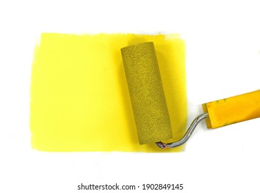 Paint roller leaving stroke of yellow color over a white background. usable for text and messages.