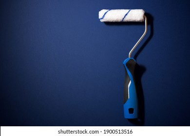 Paint roller on a blue table.