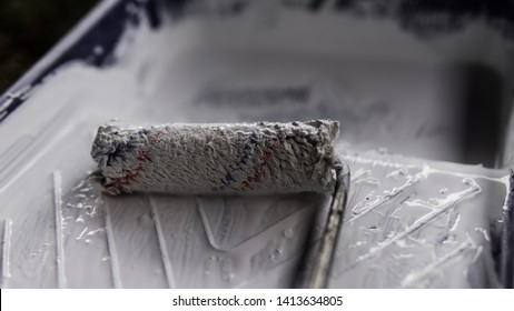 A paint roller on a plastic paint tray with a white color paint on the ground.