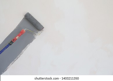 Paint roller. Painting with gray paint over a white wall