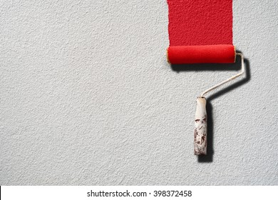 Paint roller painting with red paint on white wall with rough texture