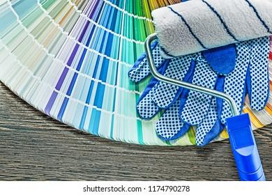 Paint roller safety gloves pantone fan on wooden board.