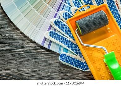 Paint roller tray safety gloves pantone fan on wooden board.
