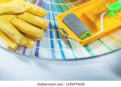 Paint roller tray safety gloves pantone fan on white background.