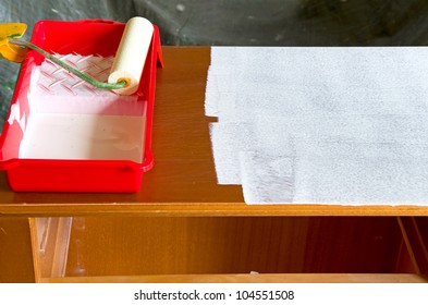 paint roller with white paint and a commode