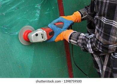 Paint and rust removing from metal plate, worker using wire brush at grinder power tool