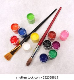 paint set and paintbrushes on textured paper