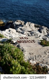 Paint sign or writing at beach saying 'no nudist'.
