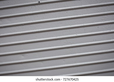 Paint smudges on the surface. The gray background. The surface of the railway car as a background element. Metal painted gray. Parallel horizontal lines. Diagonal turn