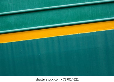 Paint smudges on the surface. The green background. Painted metal surface. Yellow lines on a green background. Metal painted green. Horizontal parallel lines. Diagonal twist