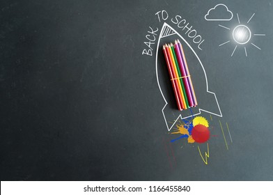 Paint splash next to a sketch of a rocket with school pencils