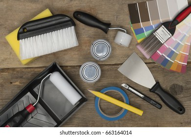 Paint swatches and painting equipment on wooden surface