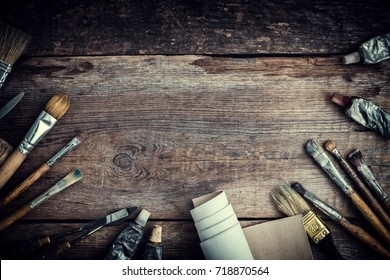 Paint tubes, brushes for painting and palette knifes on old wooden background.