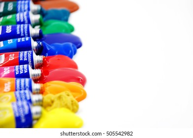 Paint Tubes made out of Tin in Various Cheerful Colors Squeezed on White Paper Background. Image is composed for design purposes like cards, brochures, magazines, websites