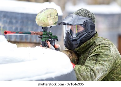 Paintball game in winter. Cool shooter behind fortification.