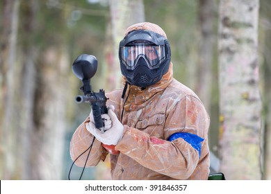 Paintball game in winter. Cool shooter with marker.