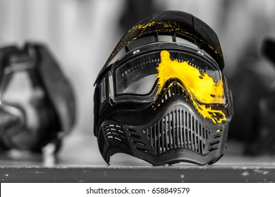 Paintball mask with yellow shot mark.