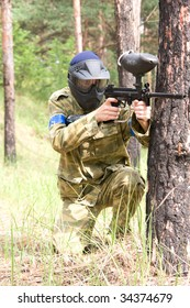 paintball player aiming in the forest