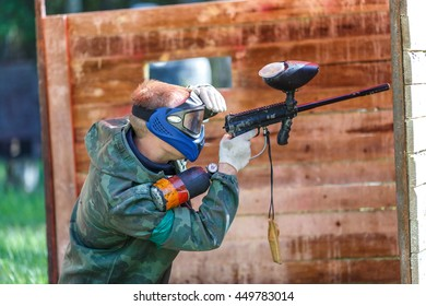 Paintball player in blue helmet shooting from paint gun