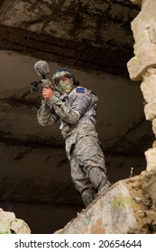 Paintball player in camouflage uniform hiding in abandoned place