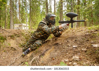 Paintball player with gun on firing position